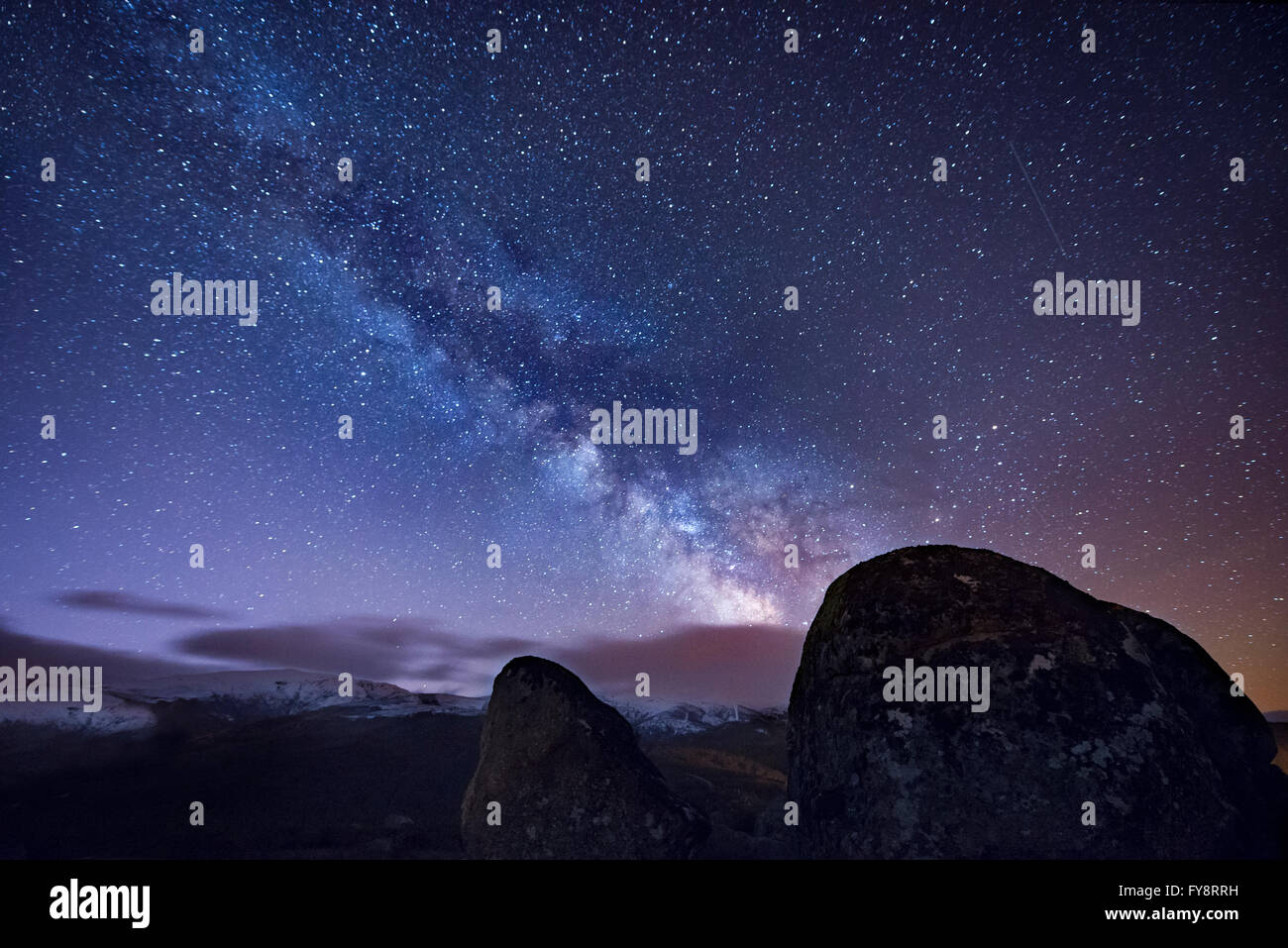 Milky way over ancient granite rocks - Stock Image