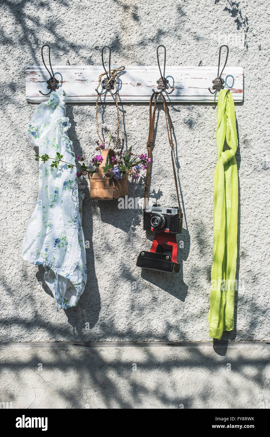 Sping items and old camera on wall coat rack - Stock Image