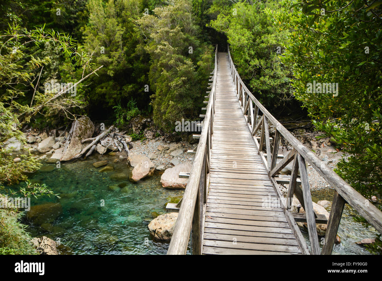 Wooden bridge crossing a clear blue river, Parque Pumalin, Patagonia, Chile - Stock Image