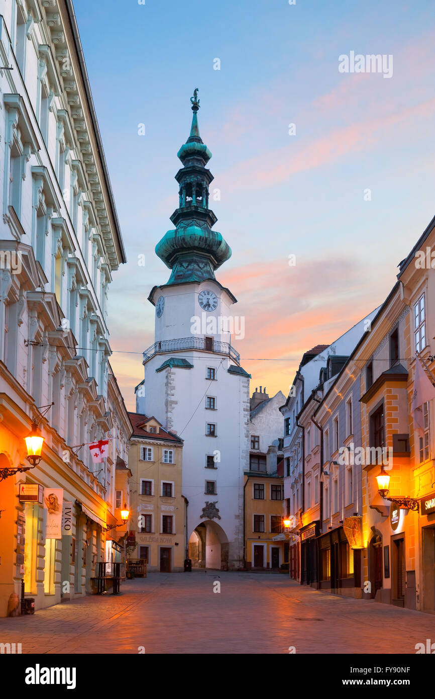 One of the main streets of the old town in Bratislava and old city gate. - Stock Image