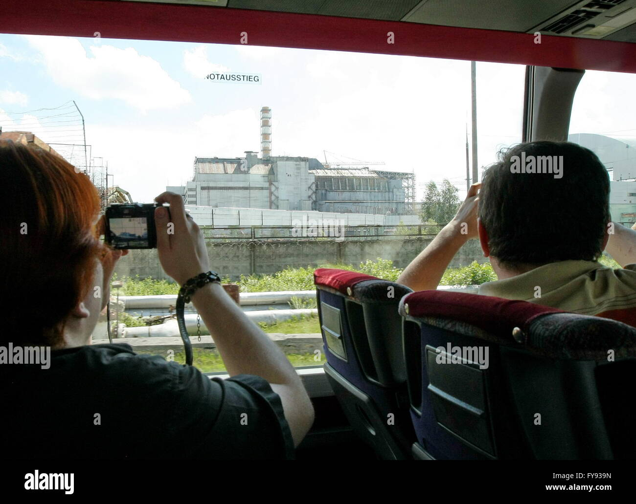CHERNOBYL, UKRAINE. Pictured in this file image are people taking pictures of a sarcophagus covering Unit 4 of the Stock Photo