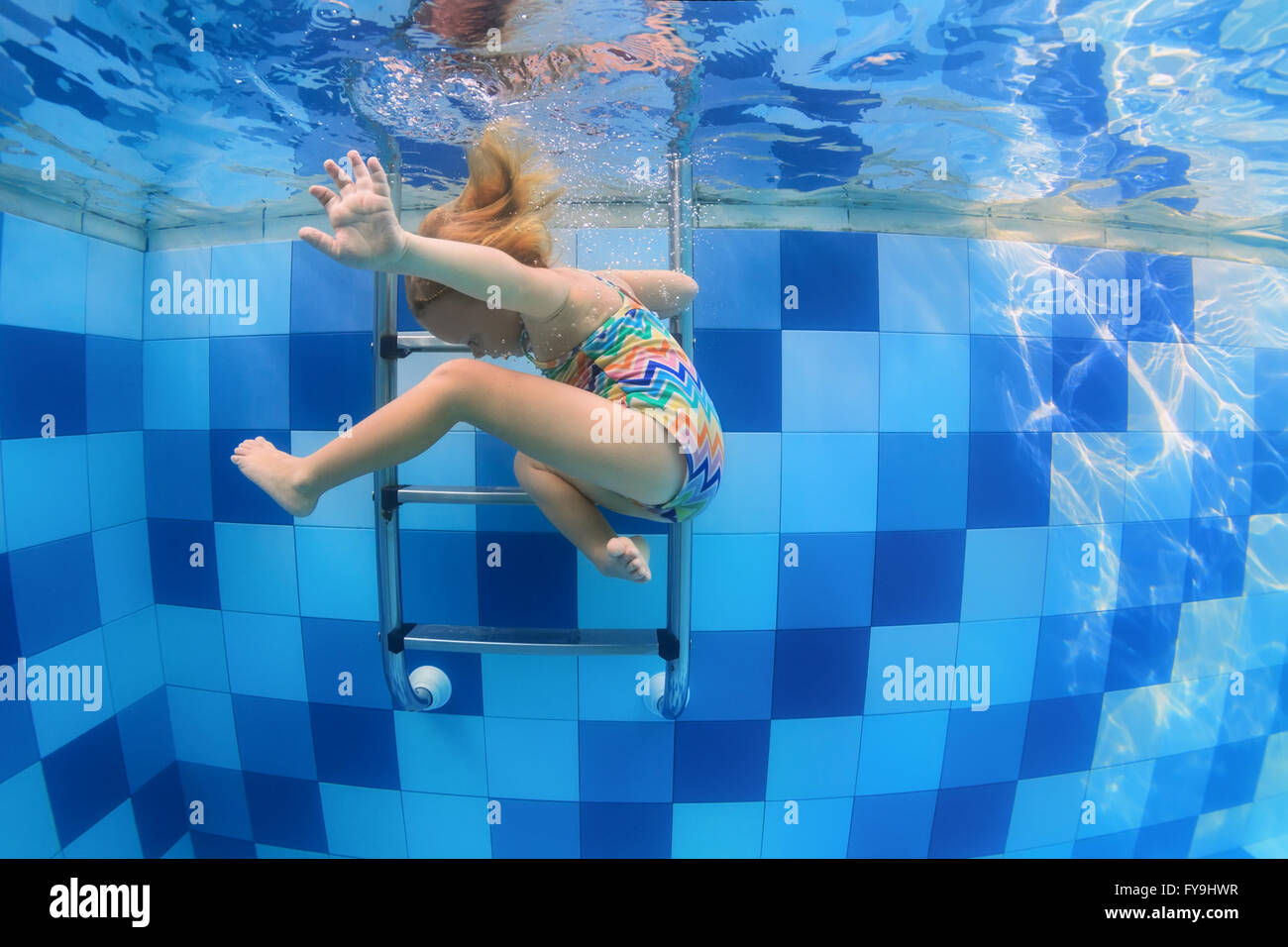 Funny photo of baby girl swimming and diving in pool with fun - jumping deep down underwater with splashes and foam. Stock Photo
