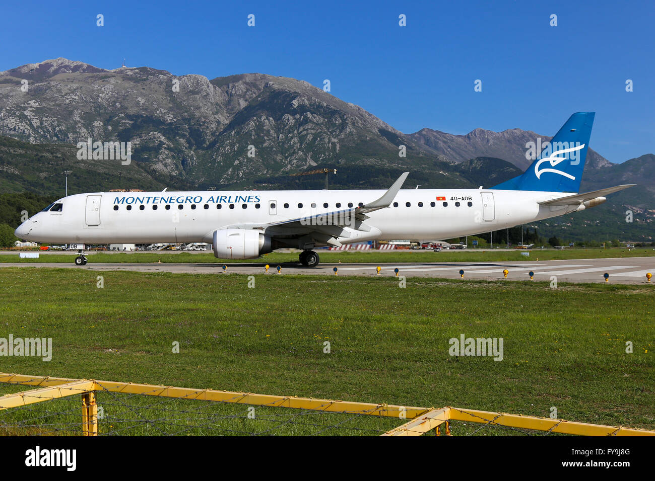 Montenegro Airlines Embraer 190 vacates runway 32 at Tivat airport. - Stock Image