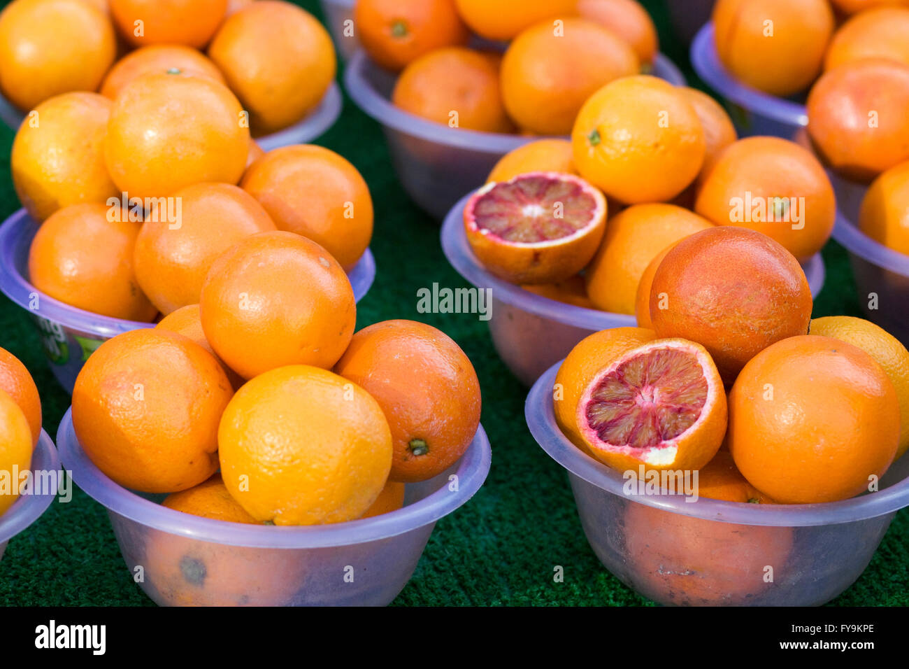 Market stall selling blood oranges in plastic bowls - Stock Image