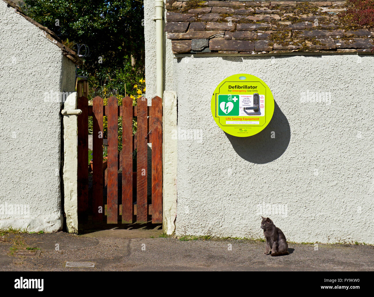 Defibrillator mounted in wall in village, England UK - Stock Image