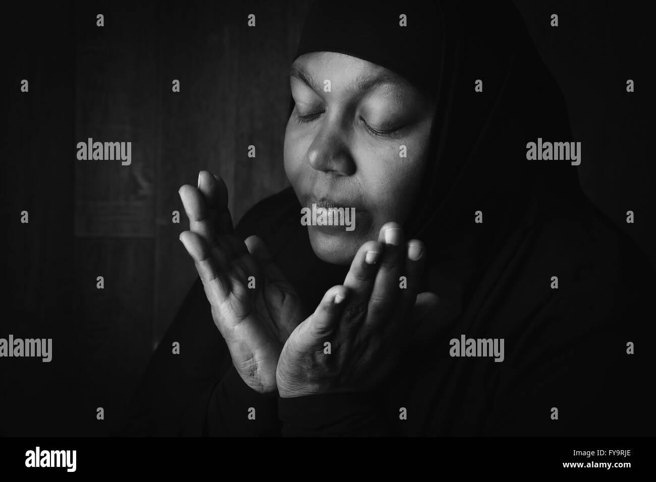 African muslim woman weiring a black veil in prayer - Stock Image