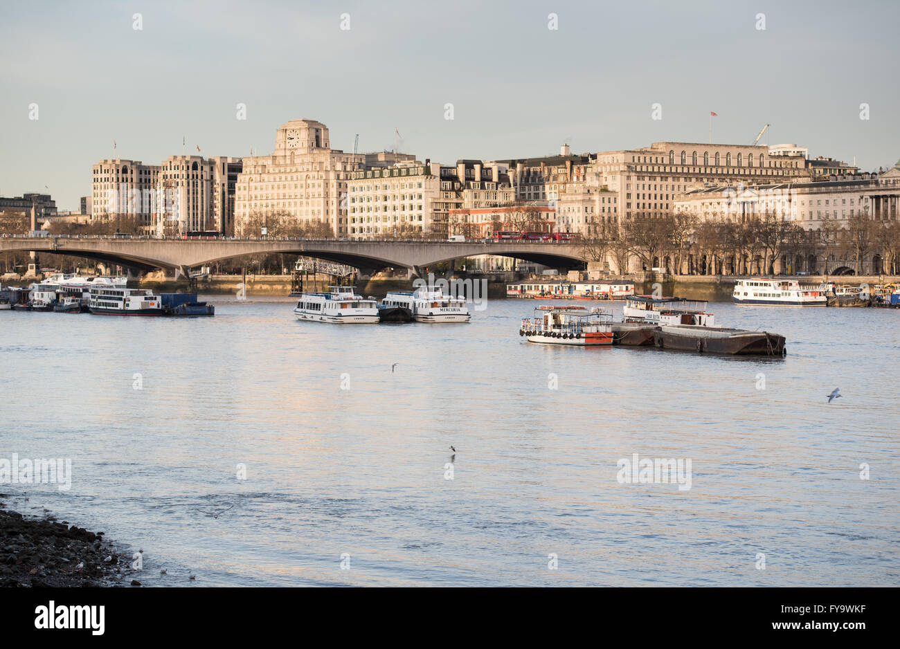 Looking west along the River Thames towards Waterloo Bridge and the buildings along Victoria Embankment - Stock Image