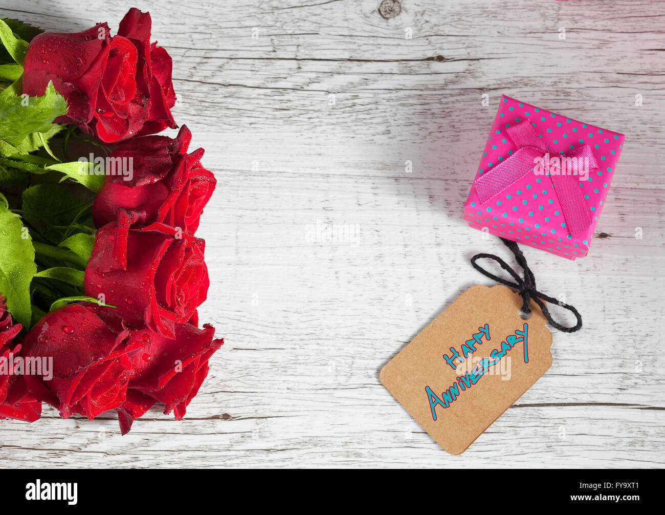 Happy Anniversary text with small gift box and red roses on white rustic wooden table. Stock Photo
