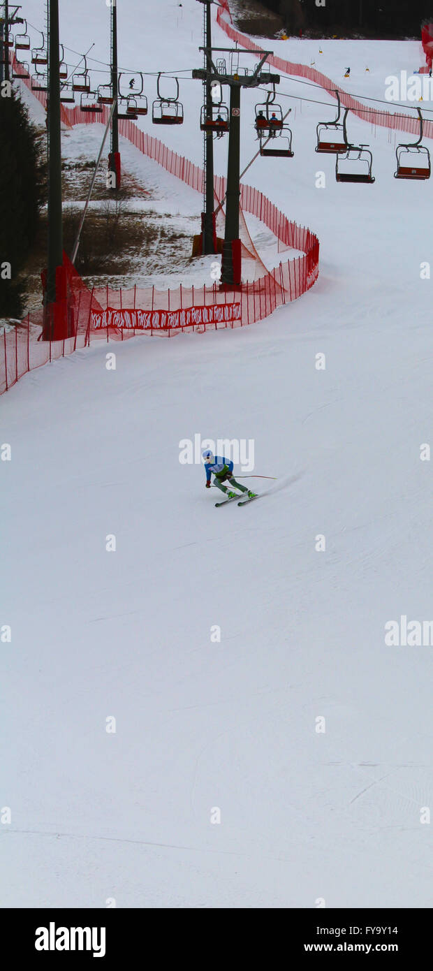 A skier tackles a downhill run in the mountain town of Pozza Di Fassa, Trentino, Italy - Stock Image