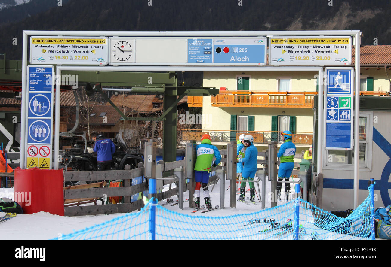 Members of the Italian National Ski Team pass through a gate to access a ski lift of a downhill slope in Pozza Di - Stock Image