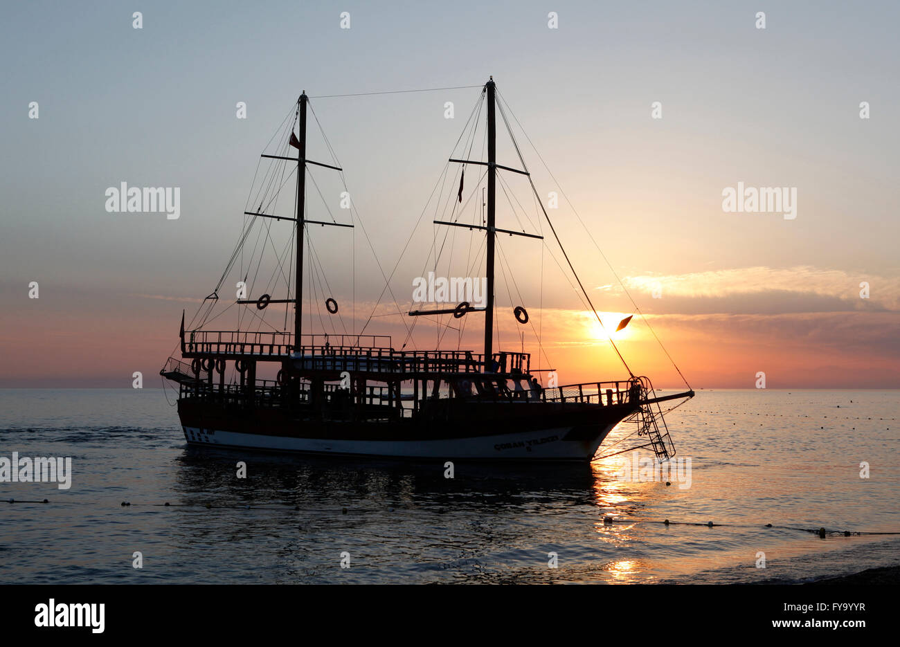 Excursion boat, sailing boat anchored on the beach at sunset, Manavgat, Antalya, Turkey - Stock Image