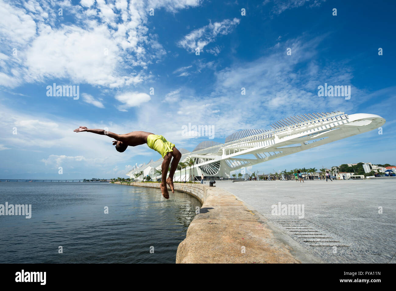 RIO DE JANEIRO - FEBRUARY 25, 2016: Young Brazilian jumps into Guanabara Bay in front of the newly completed Museum - Stock Image
