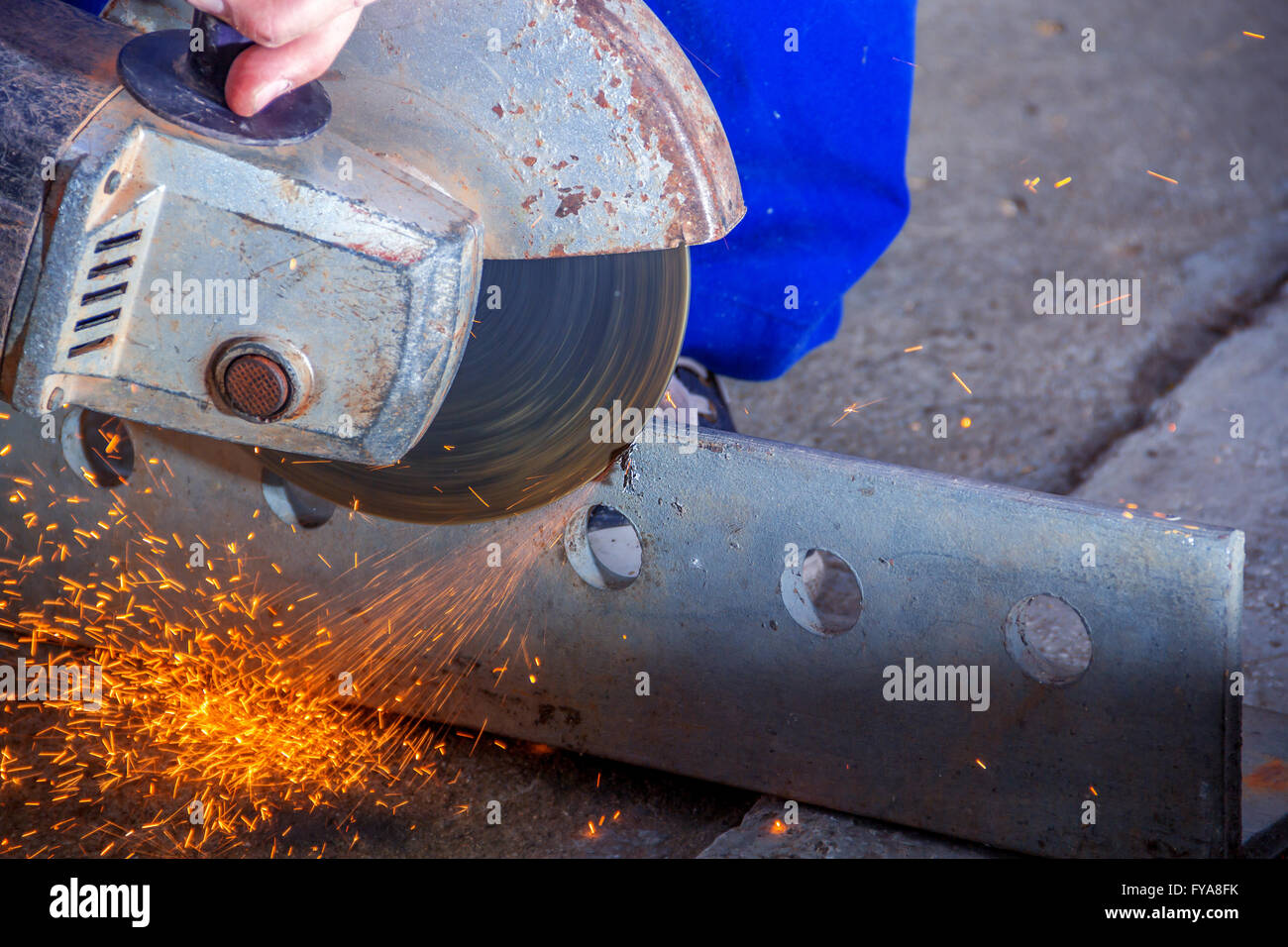 worker with angle grinder cutting steel - Stock Image