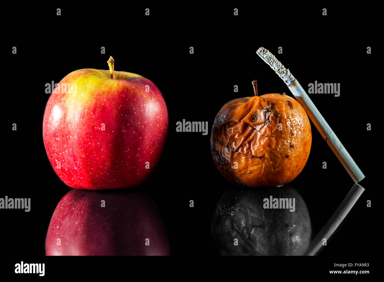 two apples and a cigarette in black background - Stock Image