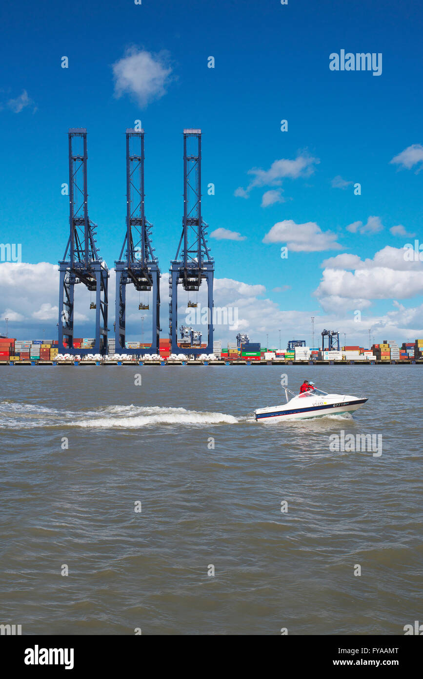 Small leisure boat motors on the North Sea past the large cranes at the port of Felixstowe as they stand empty during - Stock Image