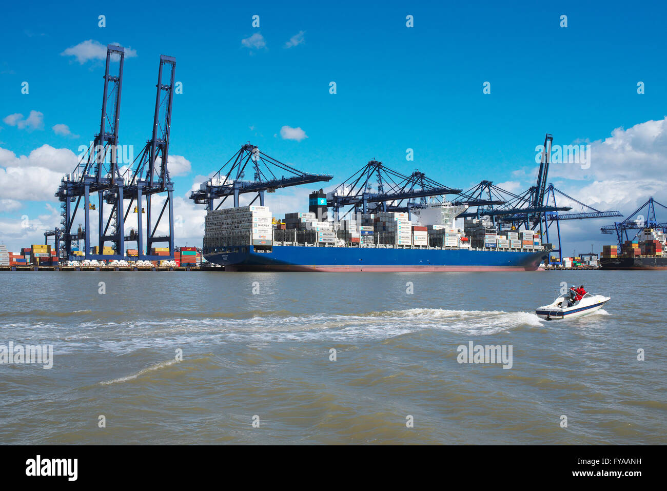 Small leisure boat motors on the North Sea past large container ships at the port of Felixstowe on the Suffolk Coast - Stock Image