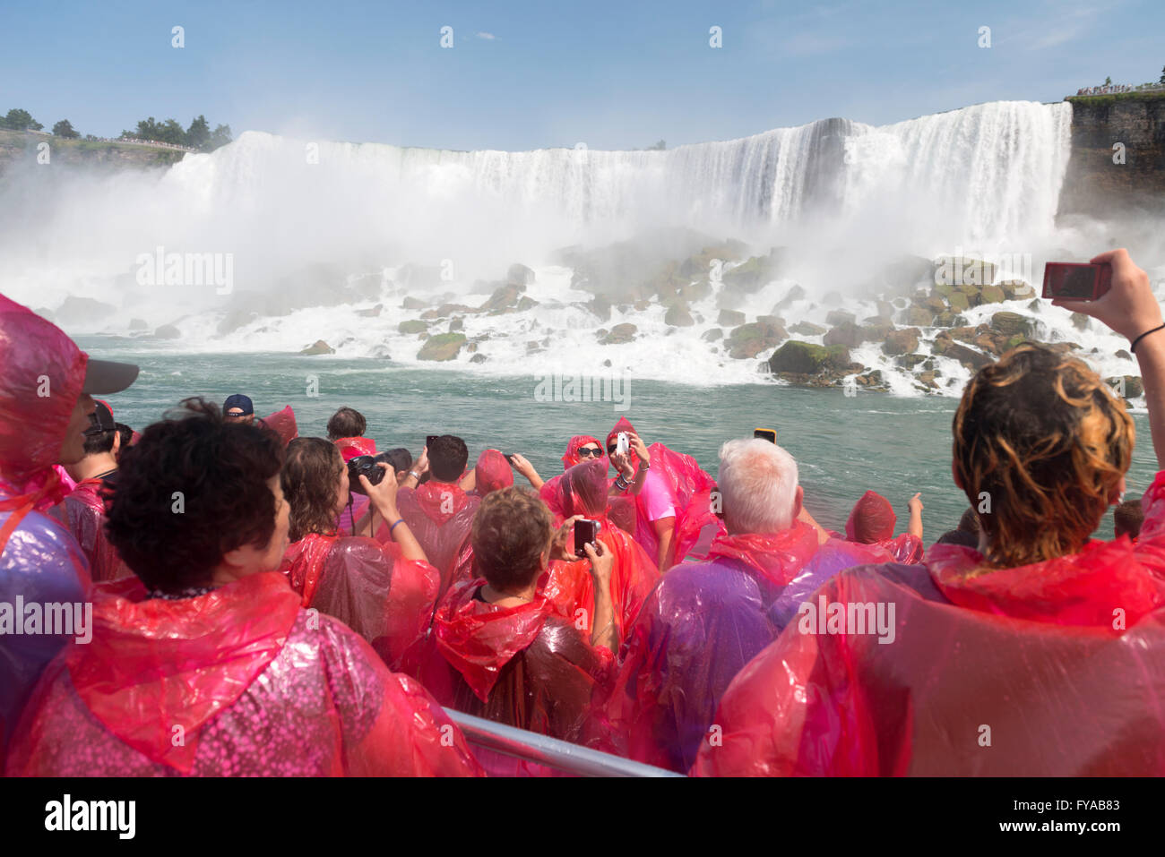 People in pink raincoats on a boat ride at Niagara Falls, Hornblower Niagara Cruises, Ontario, Canada - Stock Image