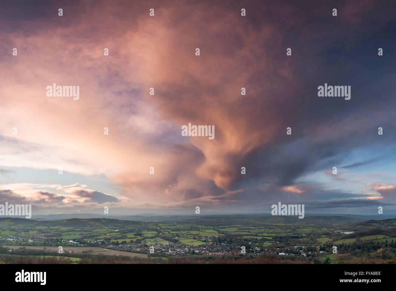 A storm cloud at sunset is being lit up by the setting sun over Colwall, Herefordshire, England. - Stock Image