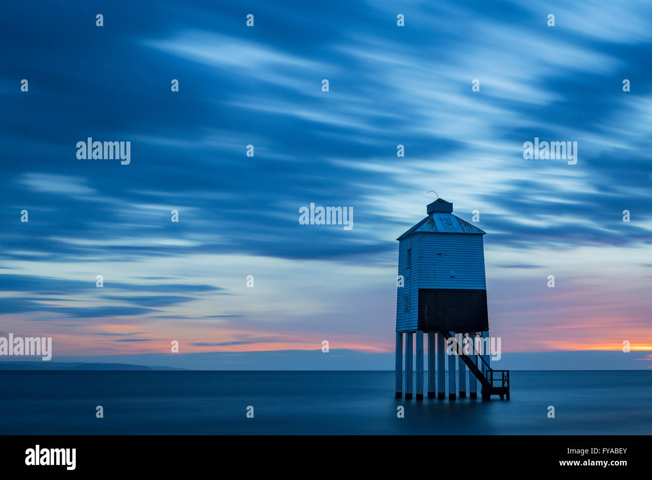 The lighthouse at Burnham-on-sea, Somerset, stands silhouetted against a pink and blue sky at sunset. Stock Photo