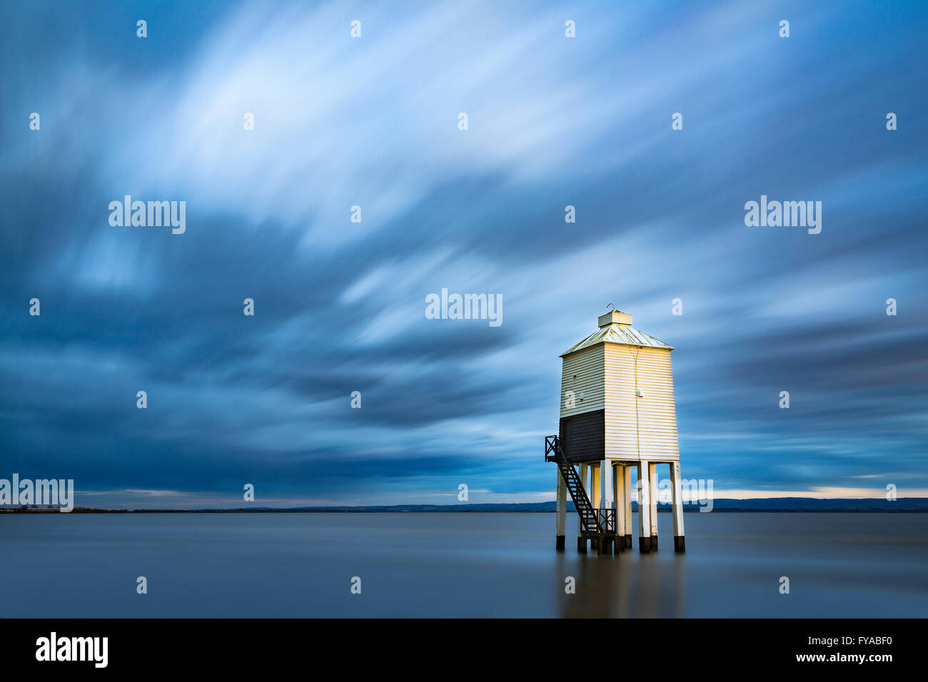 The low lighthouse at Burnham-on-sea is lit by a shaft of sunlight at sunset. A long exposure blurs the clouds and Stock Photo