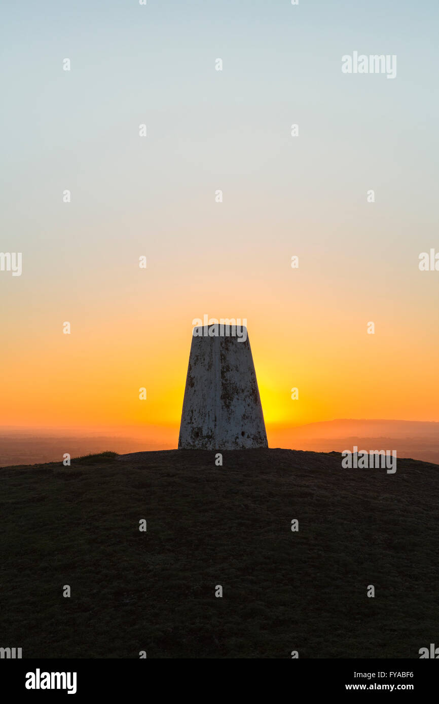 The sun rises behind a Triangulation Station or Trig Point on a clear morning. Stock Photo