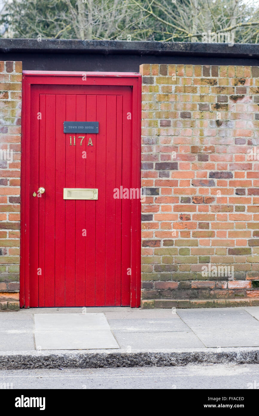 Red front door set in a wall garden entrance Stock Photo