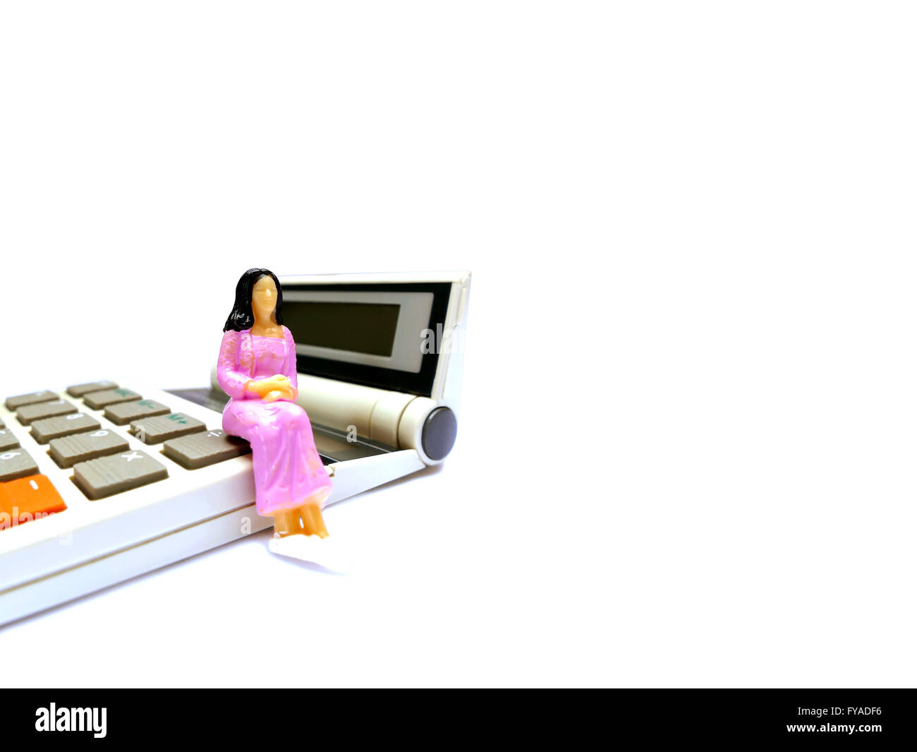 Miniature woman sitting on calculator isolated on white with room for copy space - Stock Image