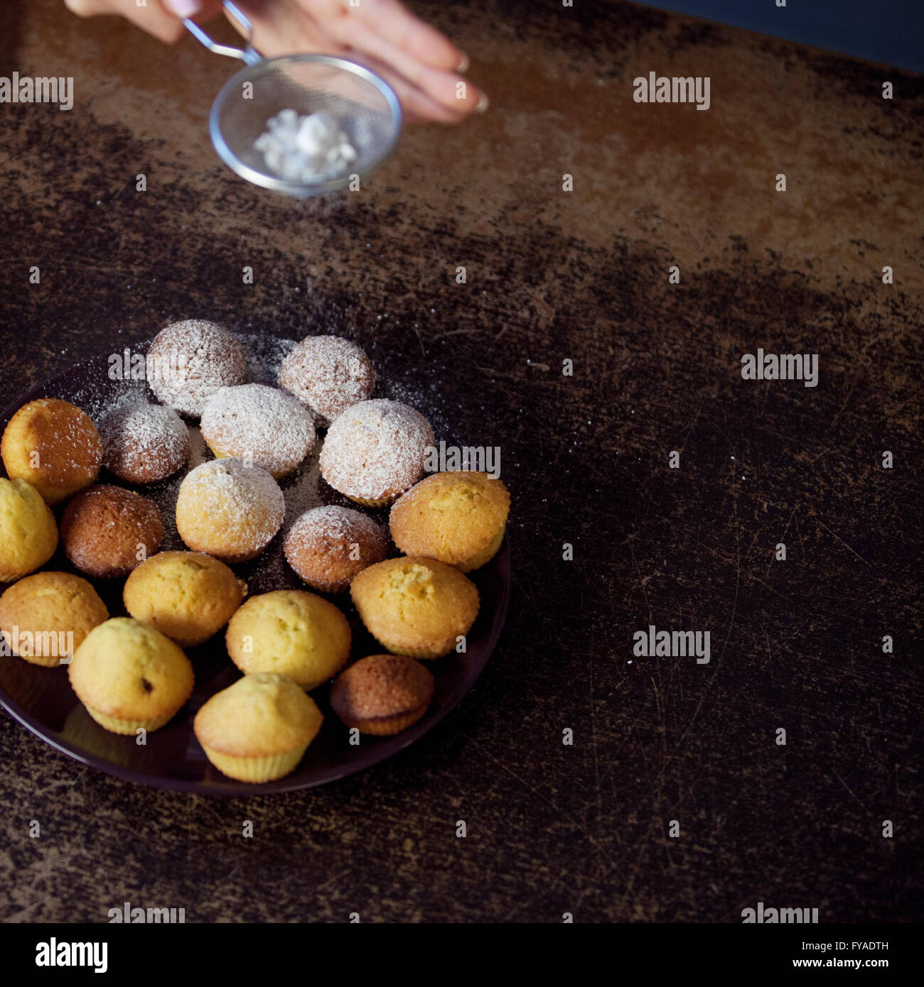 Woman's hand sprinkling icing sugar over fresh muffins. close up - Stock Image
