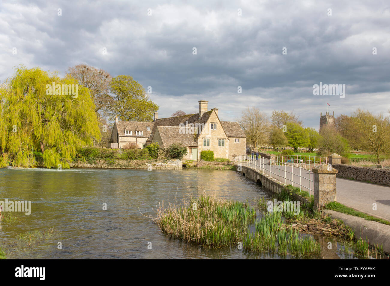Fairford Mill and the River Coln in the small Cotswold town of Fairford, Gloucestershire, England, UK - Stock Image