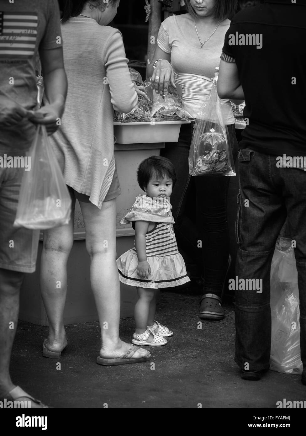 Small child in a grown up world Black and white photography - Stock Image