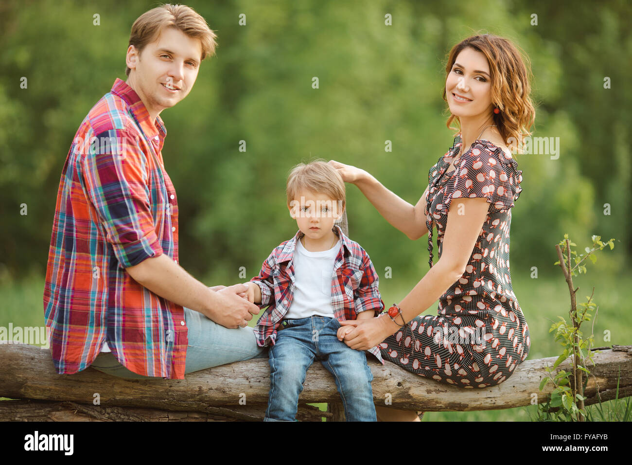 Happy family in a park - Stock Image