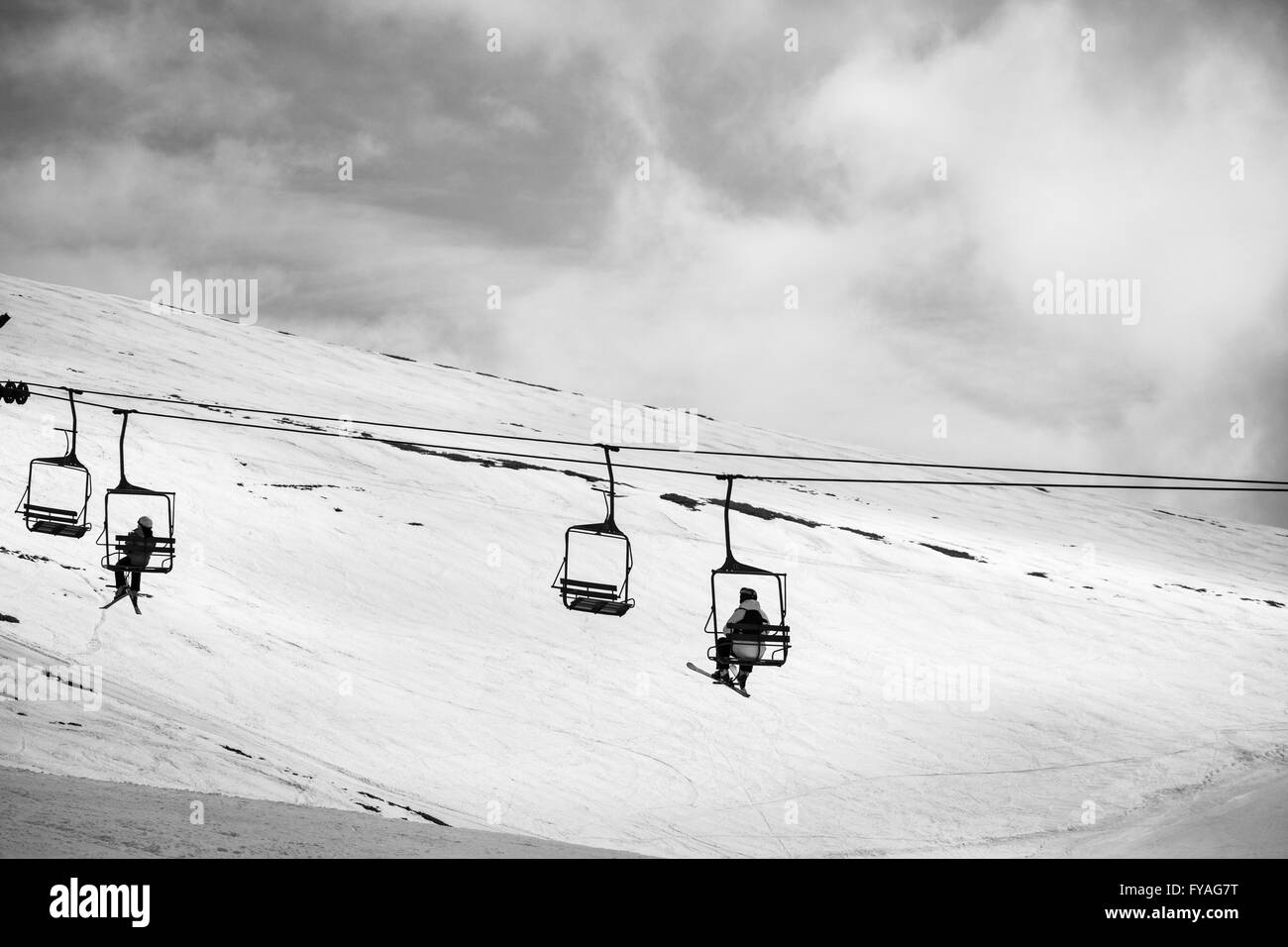 people highing up the chair lift in the top of the ski piste - Stock Image