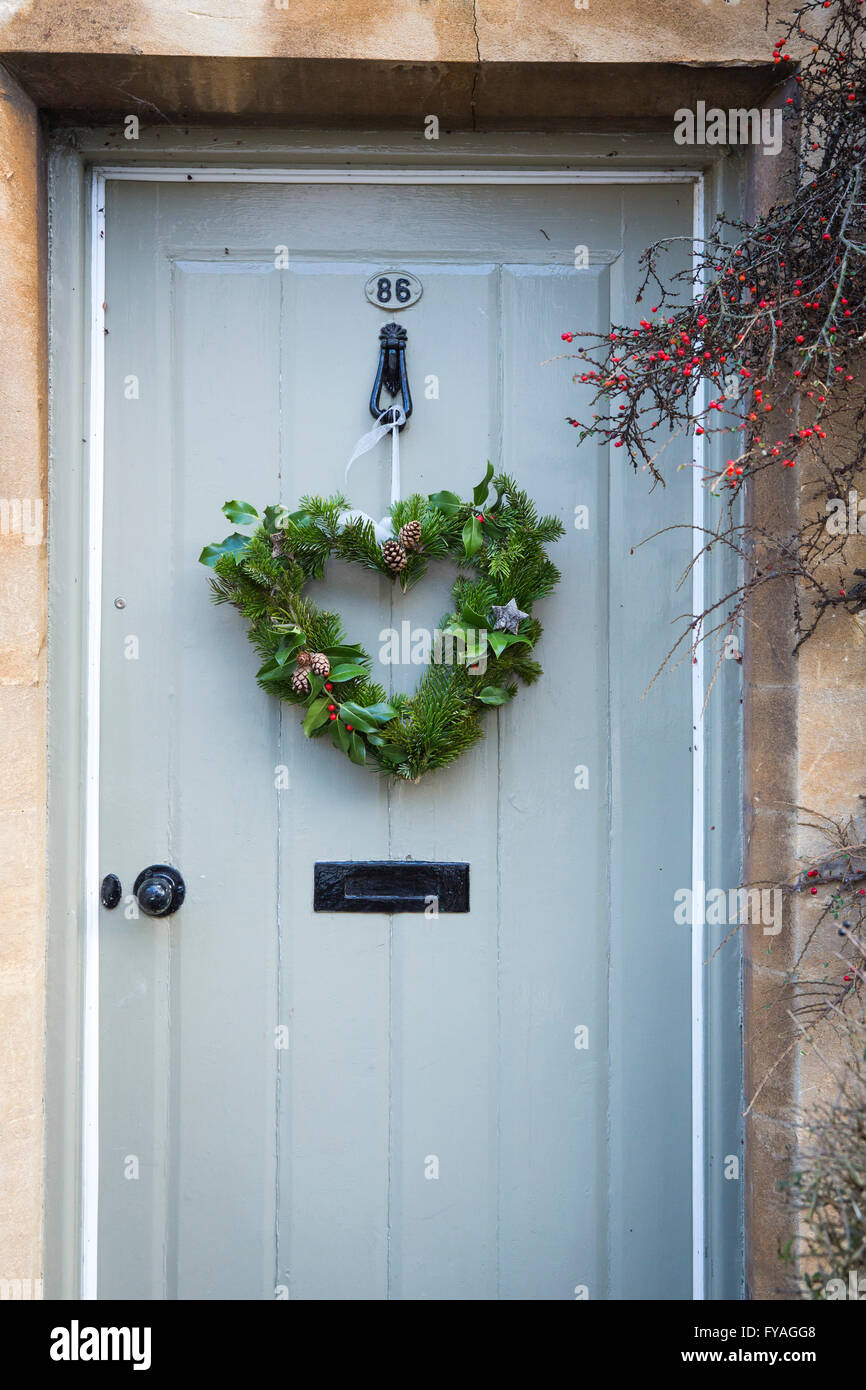 Front doors to houses at Christmas displaying festive wreaths, home made and shop bought on the doors. - Stock Image
