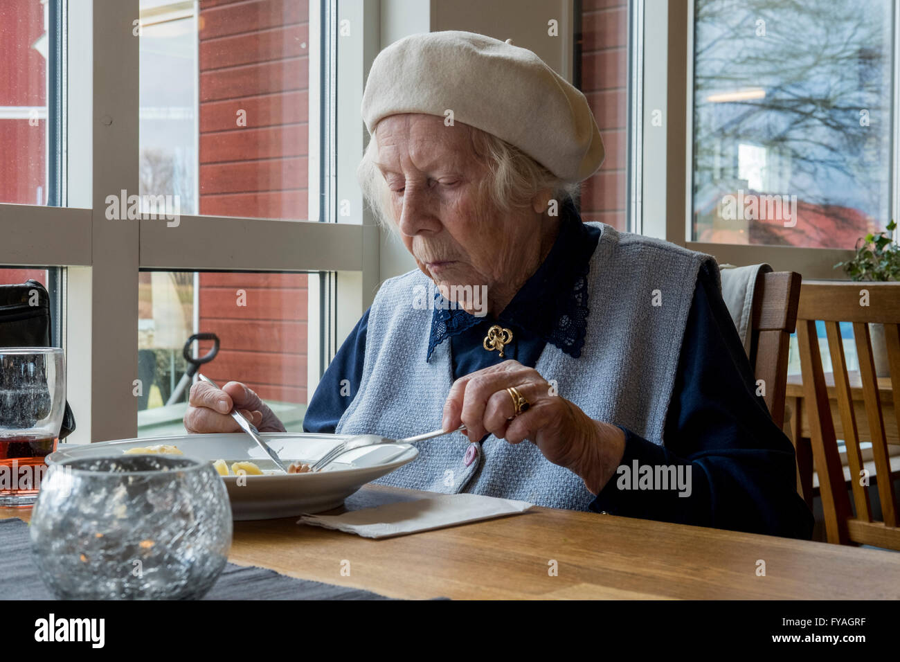Elderly woman eating lunch. - Stock Image