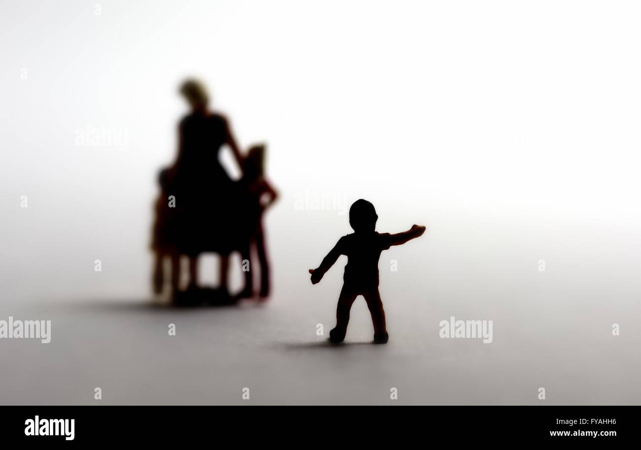 A silhouette of a small boy reaching out to a family. Adoption concept - Stock Image