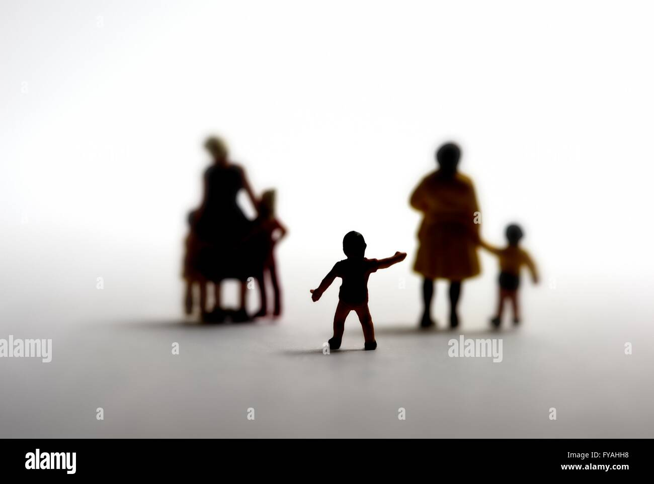 A silhouette of a small boy reaching out to families. Adoption concept - Stock Image