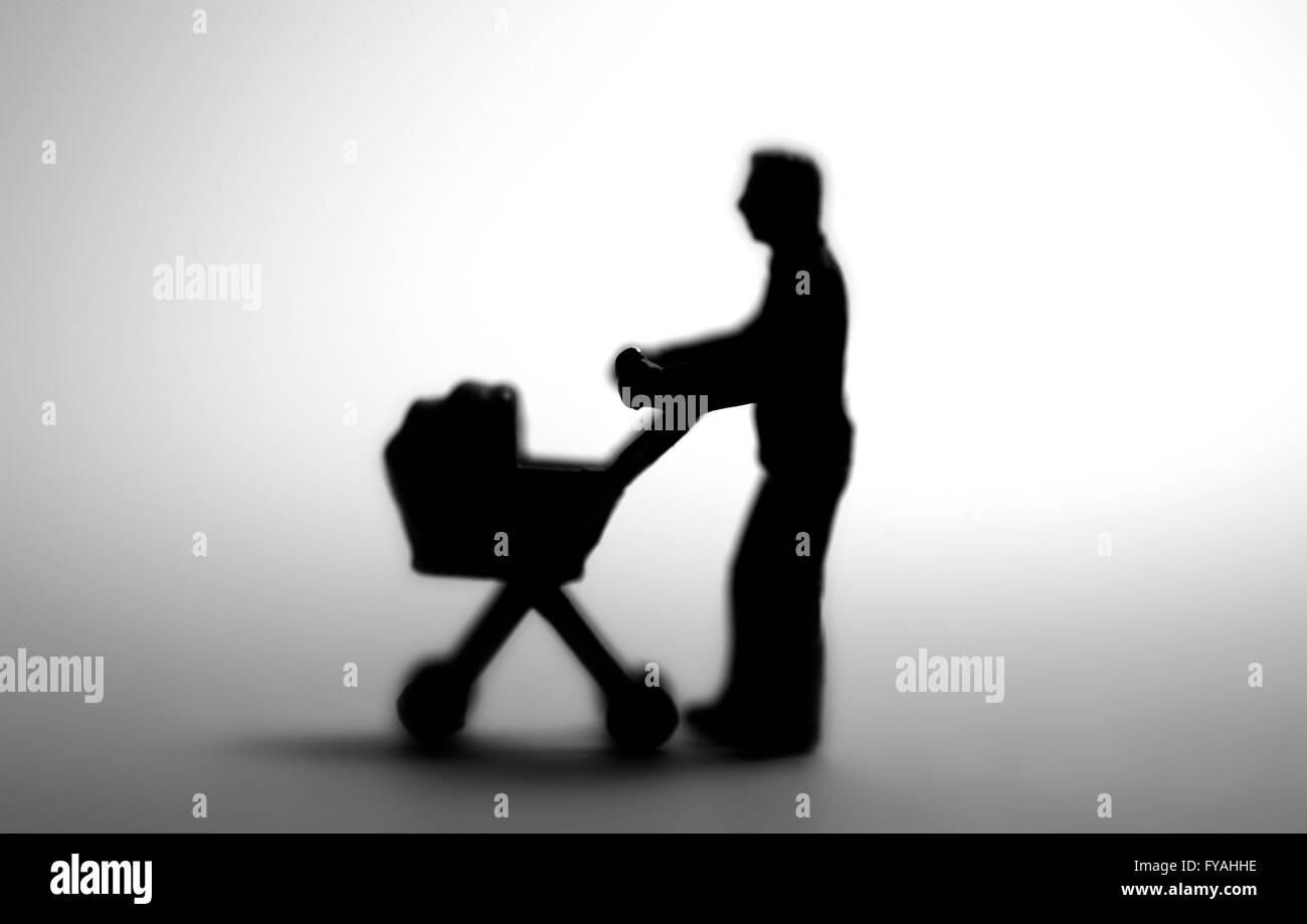 A single parent in silhouette pushing a pram - Stock Image