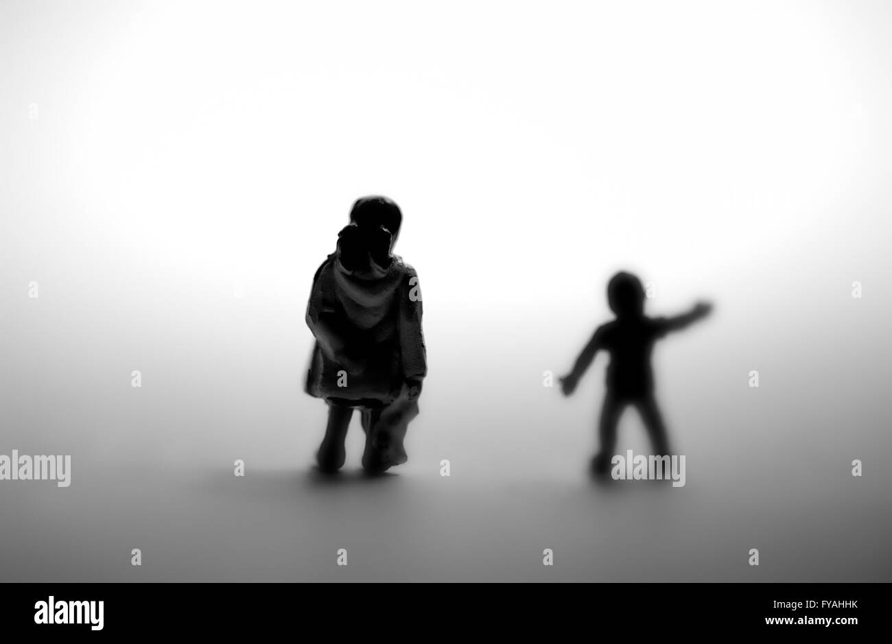 Two young children in silhouette one reaching out for help. - Stock Image