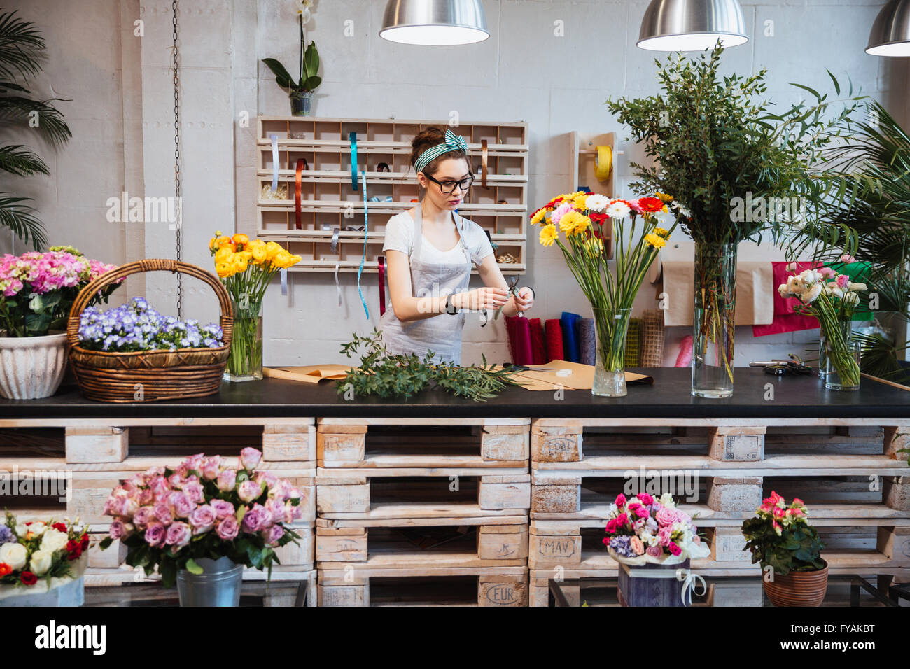Cute concentrated young female florist in glasses working in flower shop - Stock Image