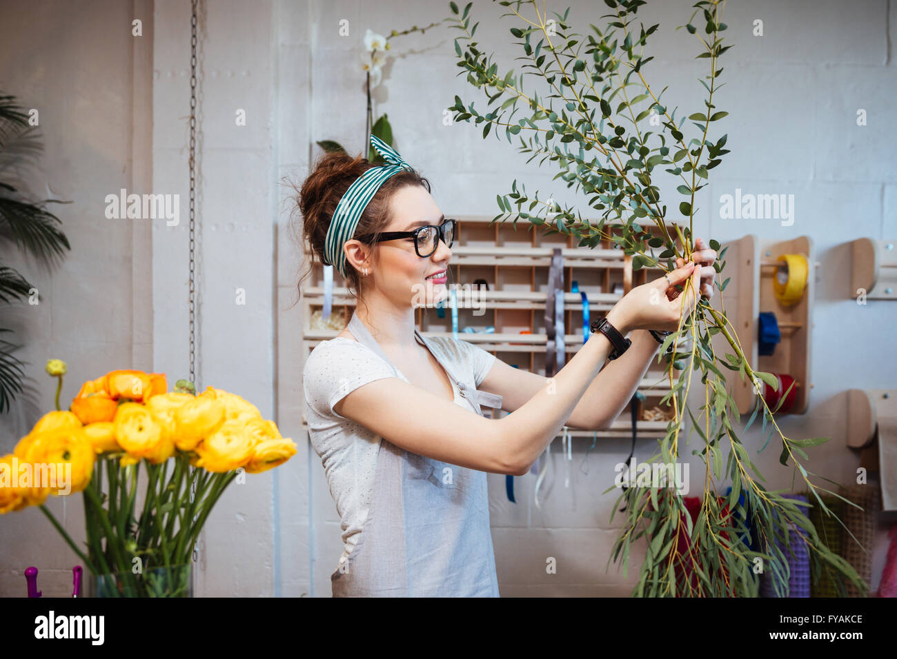 Smiling lovely young woman florist arranging plants in flower shop - Stock Image
