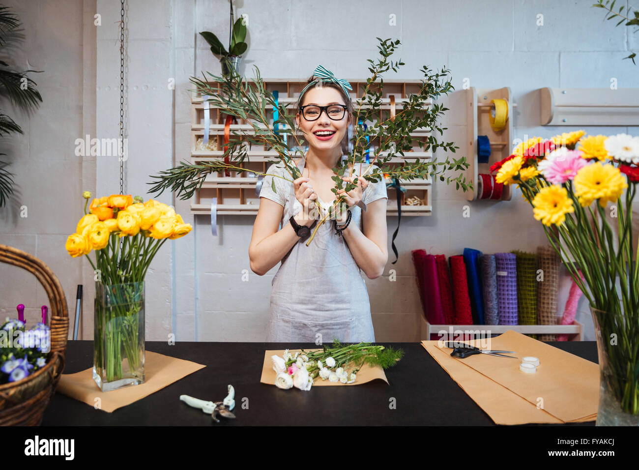 Cheerful amusing young woman florist making bouquet and having fun in flower shop - Stock Image
