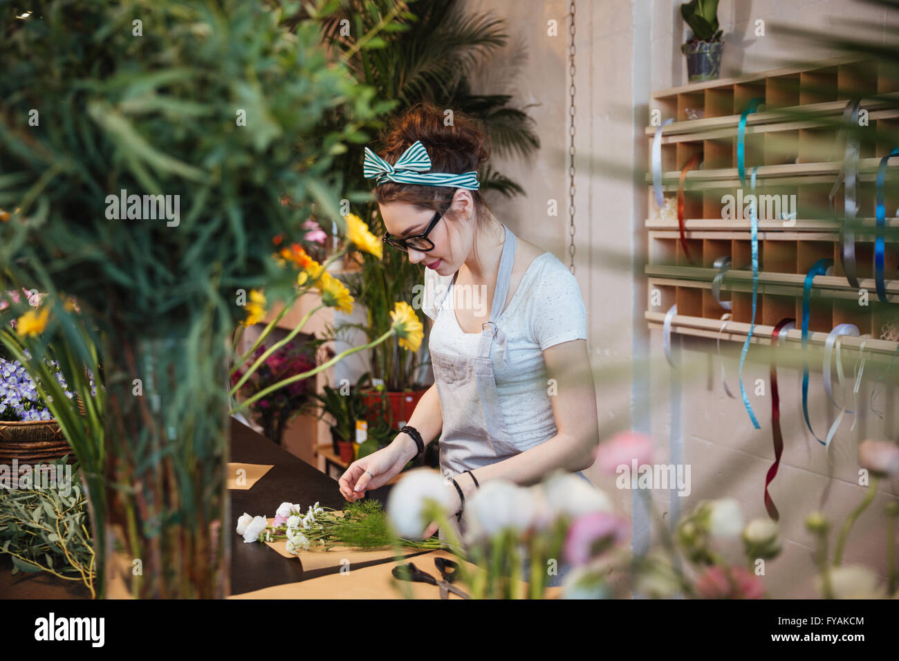 Beautiful young woman florist in apron and glasses making bouquet and working in flower shop - Stock Image