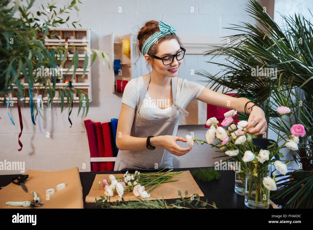 Smiling attractive young woman florist working and making bouquet in flower shop - Stock Image
