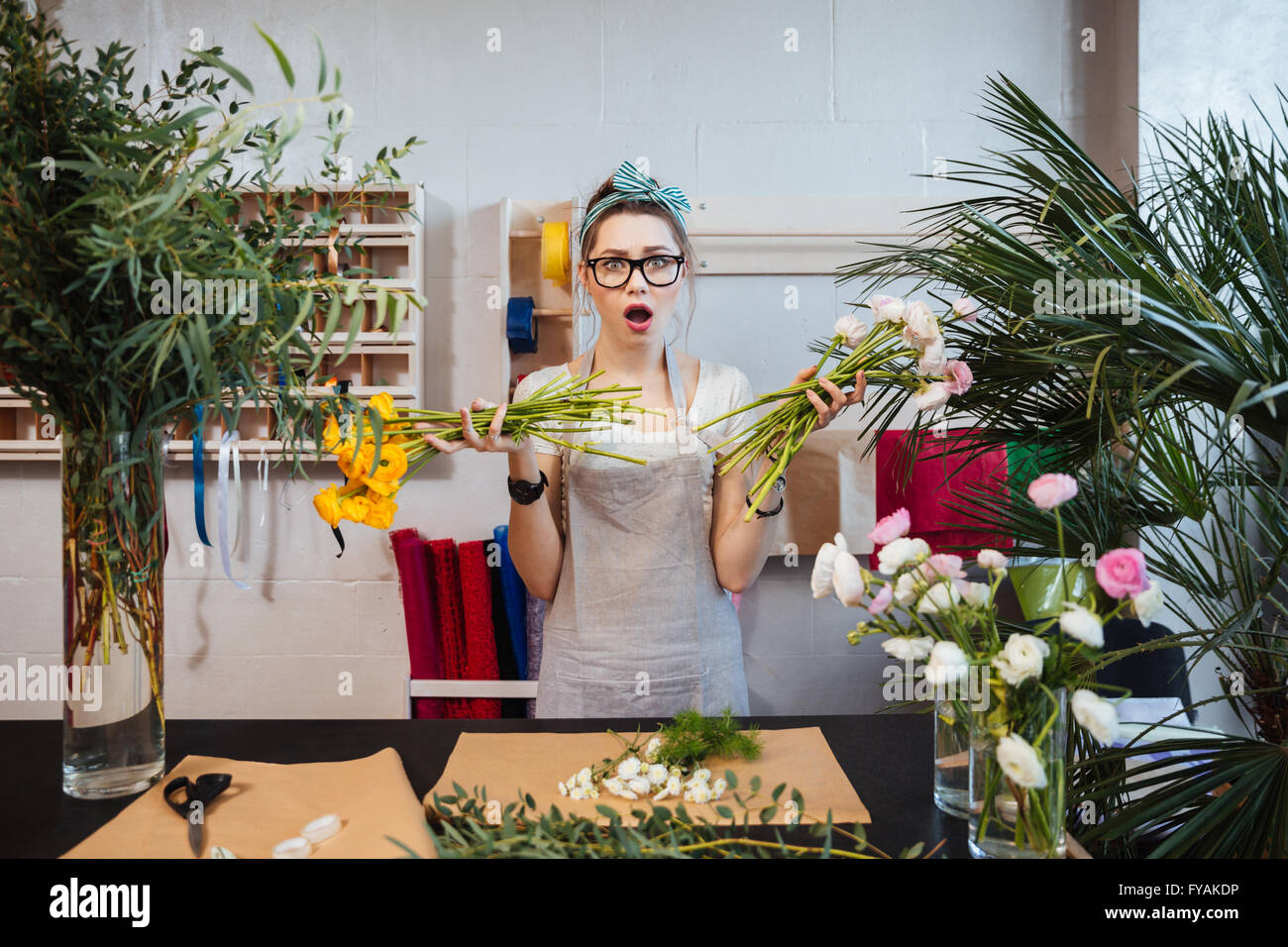 Amazed shoked young woman florist designing bouquet and holding two bunches of flowers - Stock Image