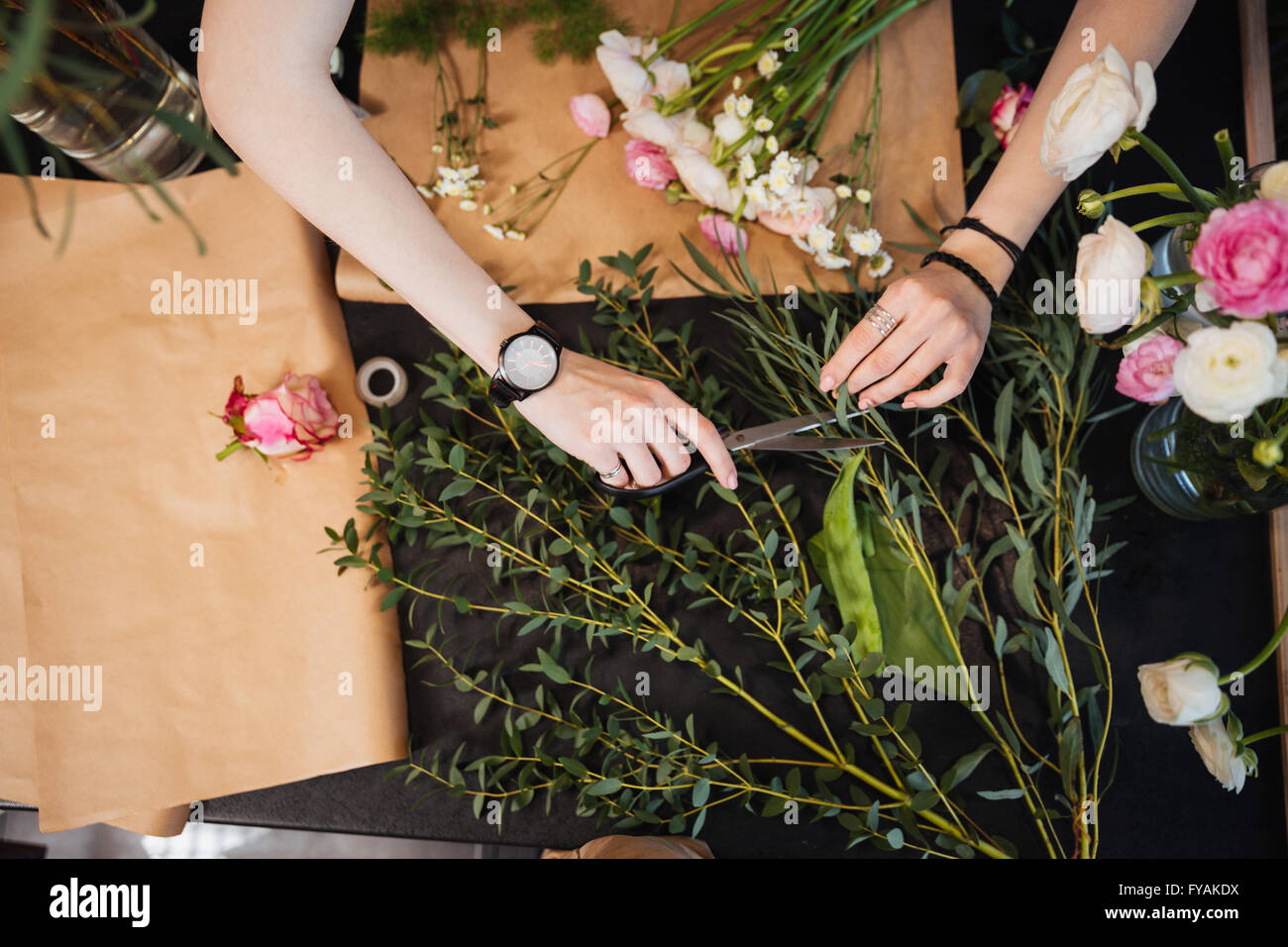 Top view of hands of young woman florist cutting flowers with scissors and designing bouquet on black table - Stock Image