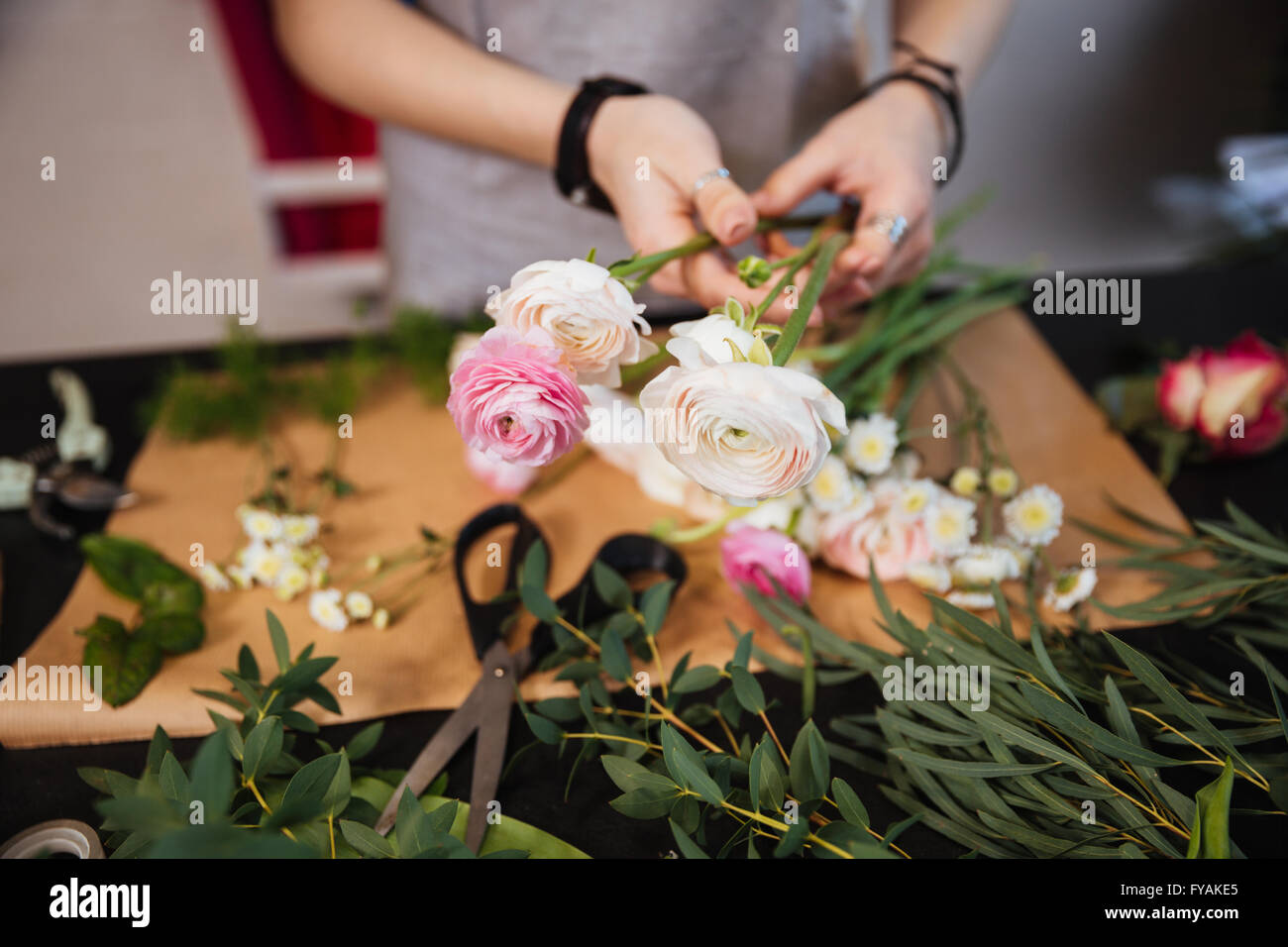 Closeup of hands of young woman florist creating bouquet of pink roses on the table - Stock Image