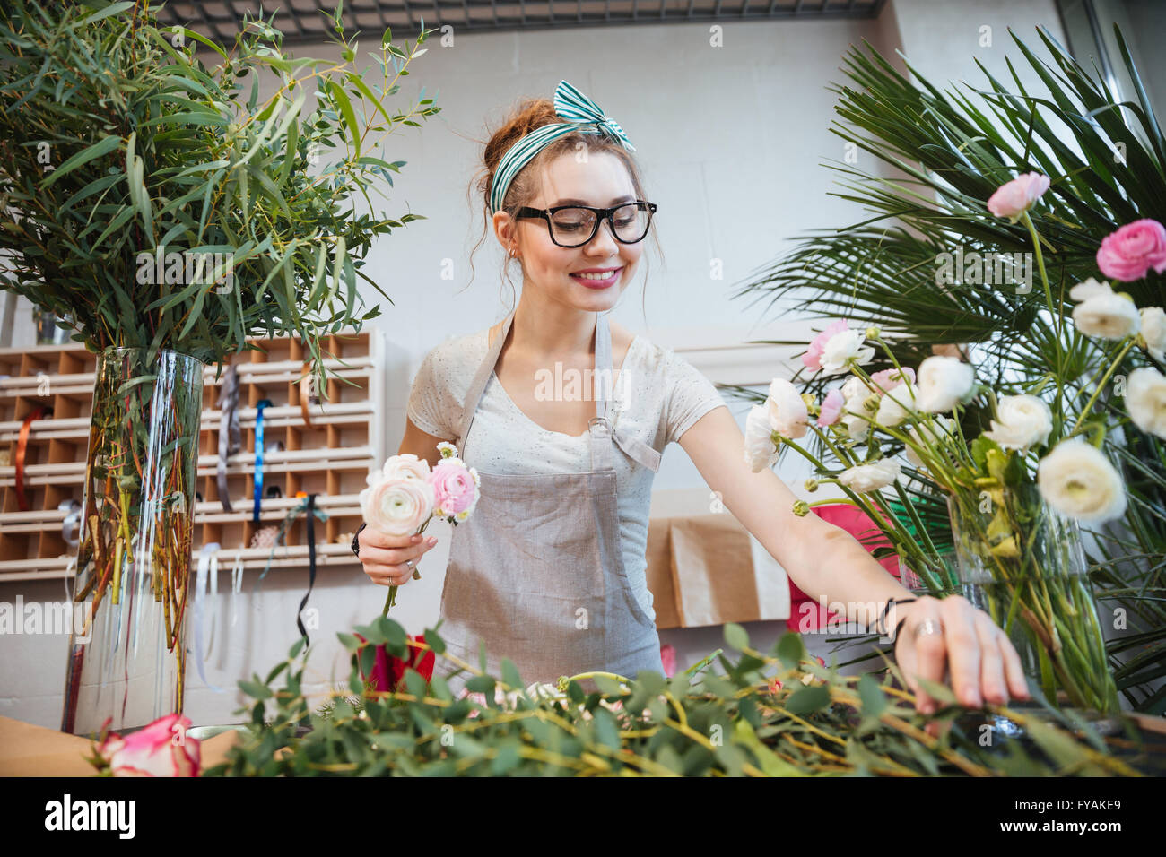 Happy lovely young woman florist making bouquet in flower shop - Stock Image