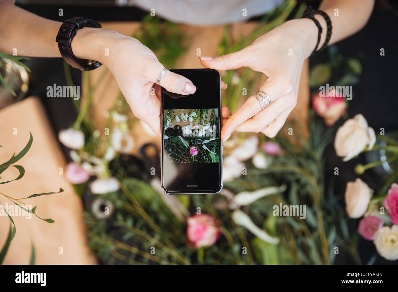Top view of hands of woman florist taking pictures of flowers with mobile phone - Stock Image