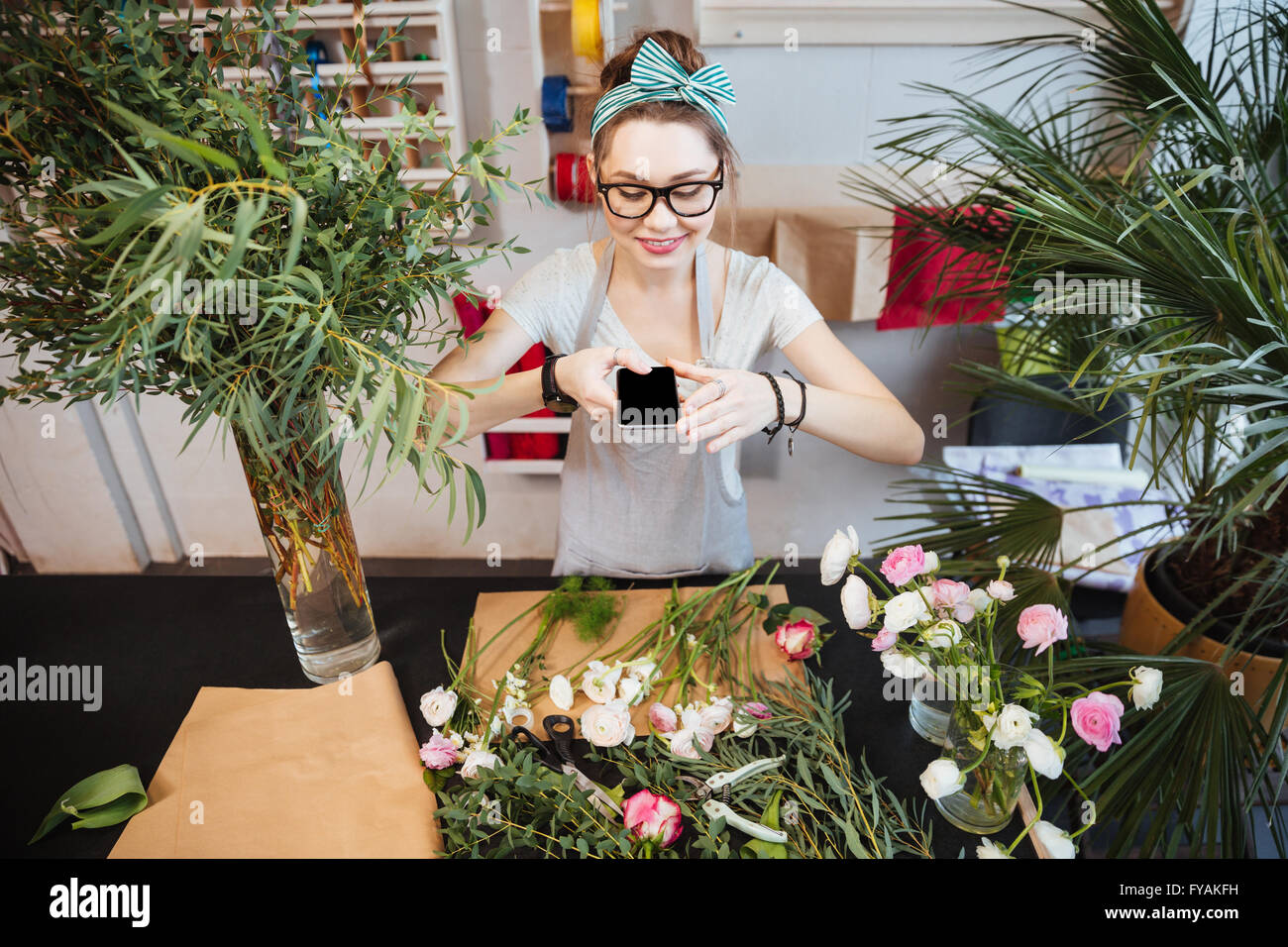 Happy beautiful young woman taking photos of flowers on table in the shop - Stock Image