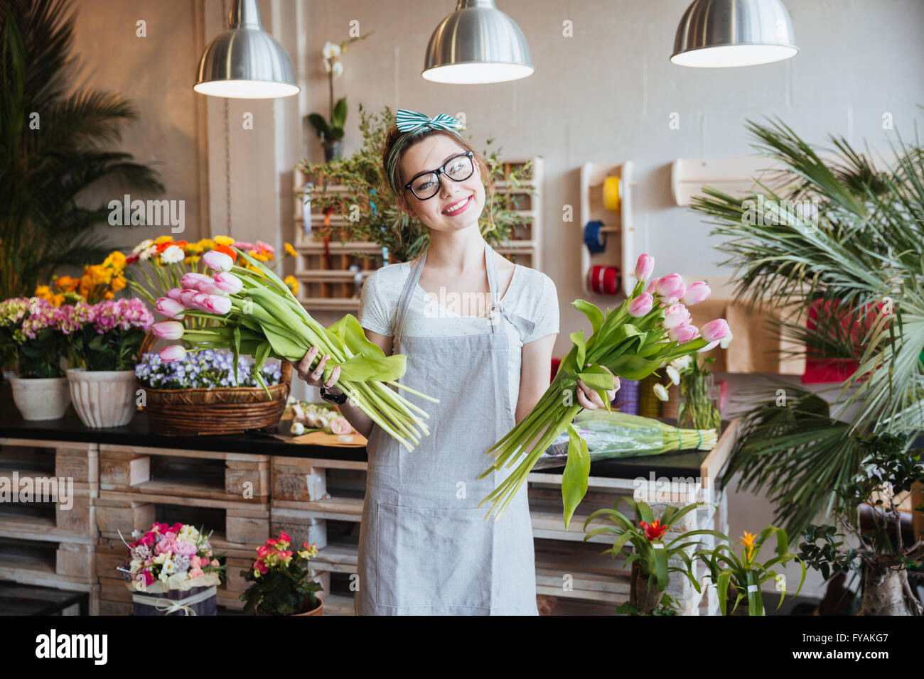 Cheerful charming young woman florist standing and holding two bunches of pink tulips in flower shop - Stock Image